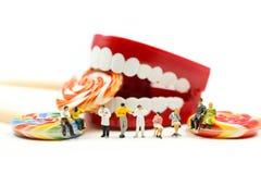 Povos diminutos: Dentista que examina os dentes de um paciente com paciente e os pirulitos doces, conceito médico dos cuidados mé imagens de stock royalty free