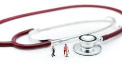 Povos diminutos: Doutor com mãe e filho no CCB do estetoscópio imagem de stock royalty free