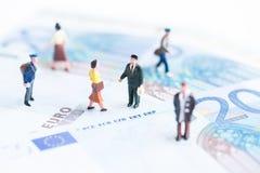Povos diminutos em cédulas do Euro fotografia de stock