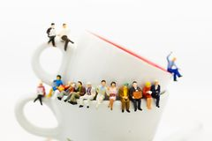 Povos diminutos: Equipe do negócio que senta-se na xícara de café e que tem uma ruptura de café Uso da imagem para o conceito do  imagens de stock