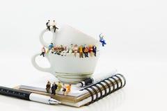 Povos diminutos: Equipe do negócio que senta-se no livro e que tem uma ruptura de café Uso da imagem para o conceito do negócio fotografia de stock