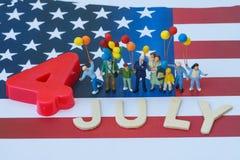 povos diminutos, família americana feliz guardando o balão e a madeira Fotografia de Stock Royalty Free