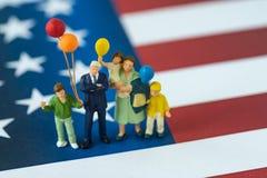 Povos diminutos, família americana feliz que guarda o balão com uni Fotos de Stock Royalty Free