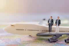 Povos diminutos - figure os businessmans que estão em airplan branco Imagem de Stock