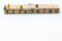 Povos diminutos: Homem de negócios que senta-se em blocos de madeira com números sequenciais Uso da imagem para o conceito do neg Fotografia de Stock