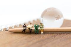 Povos diminutos: Negócio do grupo que senta-se no lápis Uso da imagem para a educação, conceito do negócio Fotografia de Stock