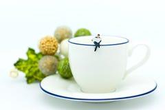 Povos diminutos: O homem de negócios que senta-se na xícara de café e tem o papel da notícia da leitura Uso da imagem para o conc Fotografia de Stock