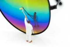 Povos diminutos: O trabalhador está pintando a cor nos vidros O uso da imagem para o projeto, cria a ideia nova, conceito do negó Fotos de Stock Royalty Free