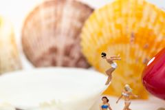 Povos diminutos: Os homens estão saltando para molhar no shell Uso para atividades, conceito da imagem do negócio do curso Imagens de Stock Royalty Free