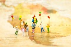 Povos diminutos: Suporte da família no mapa do mundo Uso da imagem para o dia internacional do fundo do conceito de famílias fotos de stock