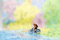 Povos diminutos: viajante que anda na língua tailandesa do mapa Usado para viajar aos destinos no conceito do fundo do negócio do fotos de stock