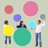 Povos diversos que guardam círculos vazios coloridos fotos de stock