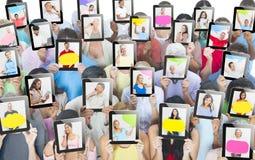 Povos diversos que guardam o dispositivo de Digitas em sua cara imagens de stock royalty free