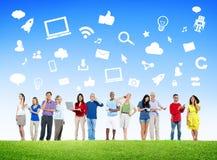 Povos diversos que usam dispositivos de Digitas com símbolos sociais dos meios Fotografia de Stock Royalty Free