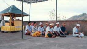 Povos do Balinese na cerimônia tradicional no templo que senta-se nos trajes filme