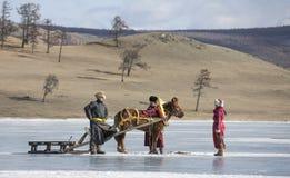 Povos do Mongolian em um lago congelado com seu pequeno trenó do hrse Fotos de Stock Royalty Free