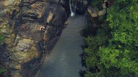 Povos do turista que mergulham e que nadam na cachoeira da montanha na paisagem aérea da floresta úmida Os povos que saltam na ág filme