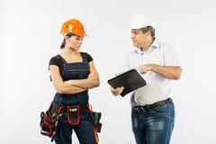 Povos dos contratantes que discutem o plano da construção sobre o fundo branco imagem de stock