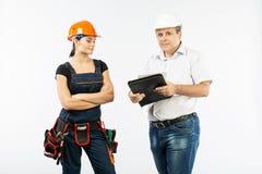 Povos dos contratantes que discutem o plano da construção sobre o fundo branco fotos de stock