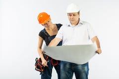 Povos dos contratantes que discutem o plano da construção sobre o fundo branco imagens de stock royalty free