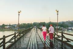 Povos dos pares de segunda-feira com o vestido tradicional na ponte de madeira na manhã em Sangklaburi, Kanchanaburi Fotos de Stock