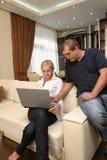 Povos dos pares que sorriem no sofá foto de stock royalty free