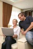 Povos dos pares que sorriem no sofá fotos de stock royalty free
