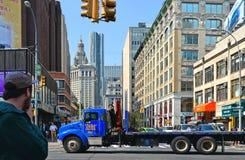 Povos e caminhão azul grande na rua na baixa de Manhattan com arquitetura velha e nova e construções na terra traseira imagem de stock royalty free
