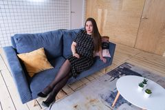 Povos e conceito do lazer - jovem mulher feliz mais o tamanho que senta-se no sofá em casa imagens de stock royalty free