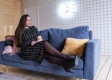Povos e conceito do lazer - jovem mulher feliz mais o tamanho que senta-se no sofá em casa foto de stock