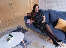 Povos e conceito do lazer - jovem mulher feliz mais o tamanho que senta-se no sofá em casa imagem de stock
