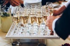 Povos elegantes que guardam vidros do champanhe no casamento luxuoso com referência a Imagem de Stock