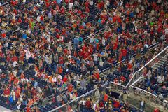 Povos em cheering vermelho durante um evento foto de stock