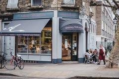 Povos em tabelas exteriores do café de Anthony Delicatessen no monte da prímula, Londres, Reino Unido fotografia de stock