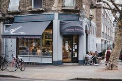 Povos em tabelas exteriores do café de Anthony Delicatessen no monte da prímula, Londres, Reino Unido foto de stock