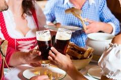 Povos em Tracht bávaro que comem no restaurante ou no bar Imagem de Stock