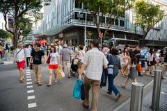 Povos em um cruzamento pedestre na estrada do pomar Fotografia de Stock