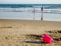 Povos em uma costa de mar do Sandy Beach e uma cubeta plástica cor-de-rosa no primeiro plano imagens de stock royalty free