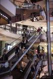 Povos em uma escada rolante em um centro de compra moderno Fotos de Stock Royalty Free