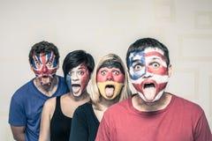 Povos engraçados com as bandeiras nas caras Fotos de Stock Royalty Free