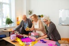Povos envelhecidos agradáveis agradáveis que envolvem presentes junto imagens de stock royalty free