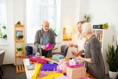 Povos envelhecidos felizes agradáveis que preparam presentes por feriados foto de stock