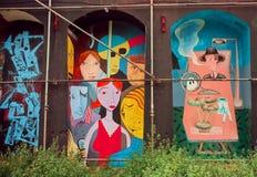 Povos estranhos na pintura mural colorida na área artística com grafittis Fotos de Stock Royalty Free