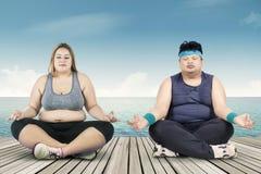 Povos excessos de peso que meditam sobre o molhe Fotos de Stock Royalty Free