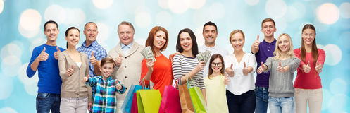 Povos felizes com os sacos de compras que mostram os polegares acima Imagem de Stock