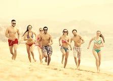 Povos felizes que correm na praia imagem de stock royalty free