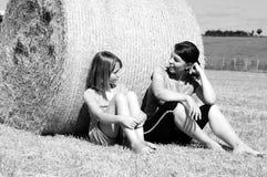 Povos felizes que falam na natureza em balas de feno Fotografia de Stock Royalty Free