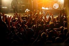 Povos felizes que levantam acima as mãos no concerto de rocha imagens de stock