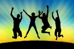 Povos felizes que saltam na alegria em um fundo do por do sol Fotografia de Stock Royalty Free