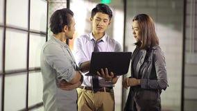 Povos incorporados asiáticos que discutem o negócio no escritório vídeos de arquivo